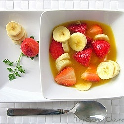Fruit salad recipe with fresh squeezed orange juice, strawberries and bananas.